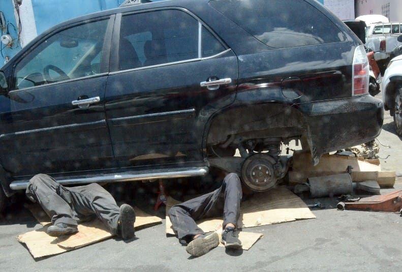 Mecánicos trabajan debajo de un vehículo estacionado sobre una acera de la calle 33.