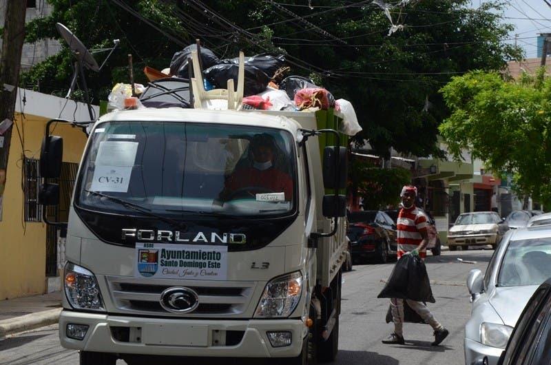 Un obrero recoge la basura y la lleva al camión en una calle del municipio Santo Domingo Este.