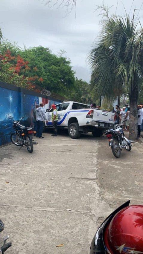 Una unidad de la Policía y varios curiosos en la escena donde un hombre atacó a tiros a varias personas en Higüey.