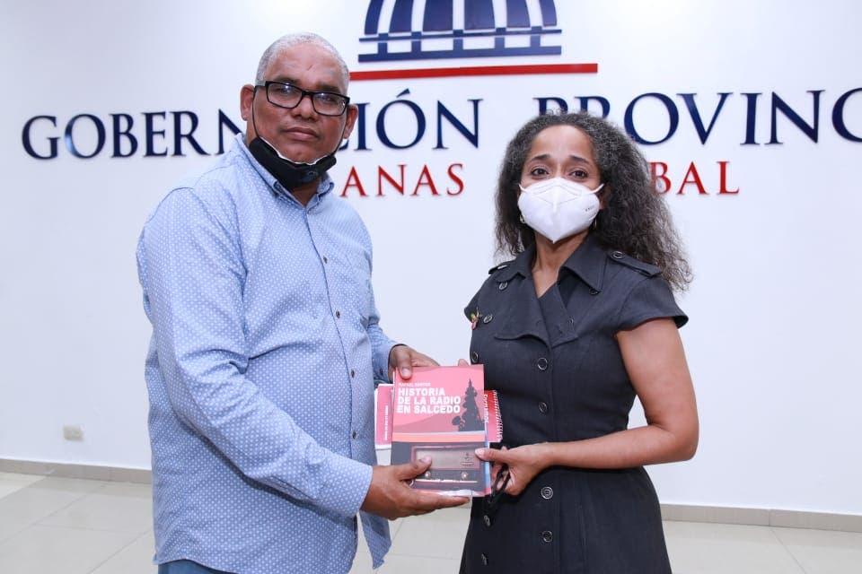 El periodista Rafael Santos entrega uno de sus libros a la embajadora Julissa Reynoso, en una actividad en Salcedo.
