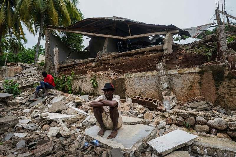En la foto de archivo, un hombre se agacha sobre los escombros del hospital destruido por el terremoto en Fleurant, Haití, tres días después de que el terremoto de magnitud 7,2 azotara la nación caribeña. Las tragedias gemelas en lados opuestos del mundo están acumulando miseria en personas que han visto mucho más de lo que les corresponde. En Haití, otro terremoto y otra tormenta golpearon a un país excepcionalmente mal equipado para manejarlos (AP Photo / Fernando Llano)