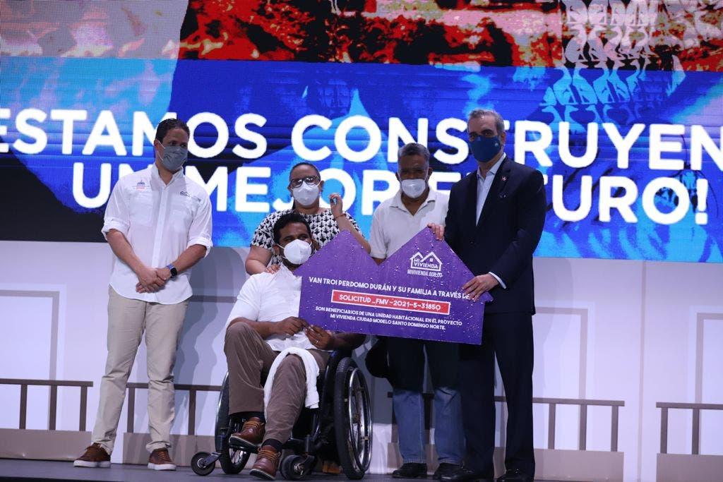 Abinader hace entrega de manera simbólica de un bono del plan Mi Vivienda a un discapacitado.