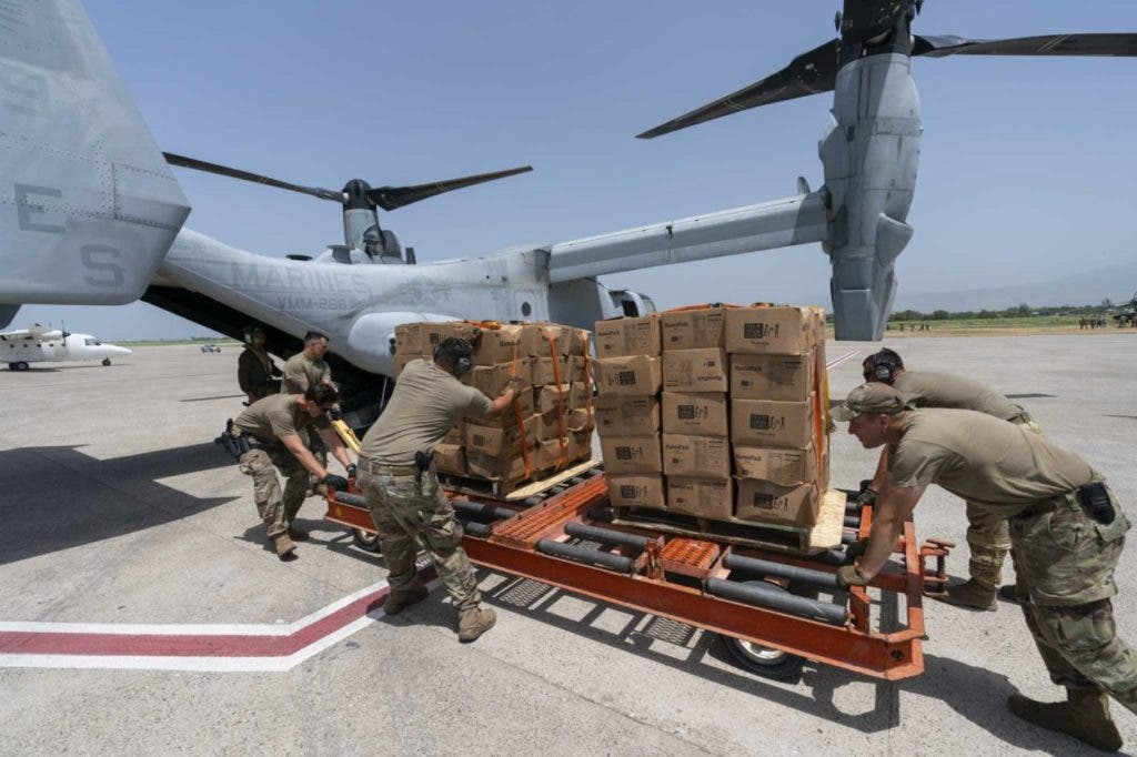 Varios militares cargan cajas de comida en un avión VM-22 Osprey en el Aeropuerto Internacional de Toussaint Louverture