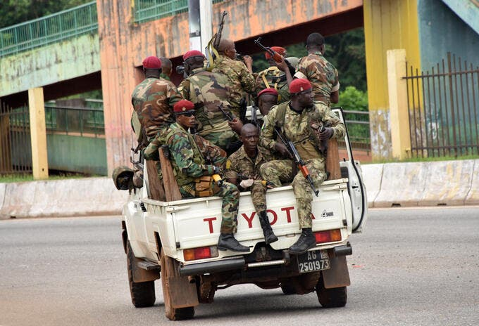 Members of the Armed Forces of Guinea drive through the central neighbourhood of Kaloum in Conakry on September 5, 2021 after sustainable gunfire was heard. - Gunfire was heard in Conkary in the morning and troops were seen on the streets, witnesses told AFP. There was no immediate explanation for the incidents in Conakry's Kaloum peninsula, where the presidency, various institutions and offices are located. (Photo by CELLOU BINANI / AFP)