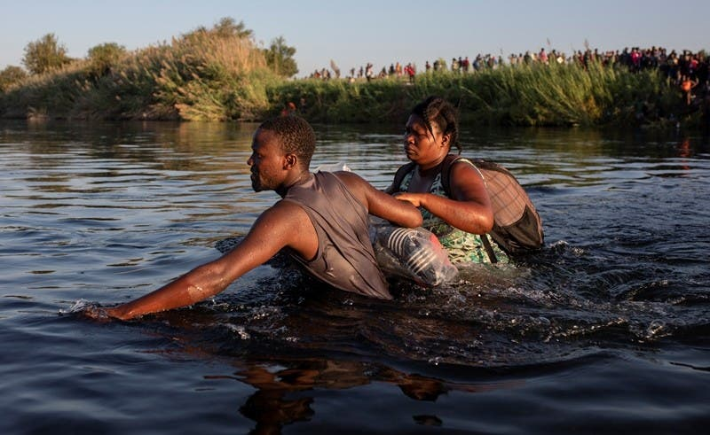Dos migrantes haitianos cruzan el rí¬o Bravo desde Del Rí¬o, Texas, hacia Ciudad Acuña, México, para evitar ser deportados por Estados Unidos. (AP Foto/Félix Márquez)